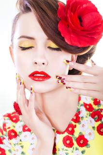 Brunette woman in yellow and red dress with poppy flower in her hair, poppy ring and creative nails, closed eyes on white background
